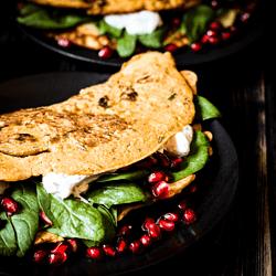 Rezept für ein leckeres veganes Kartoffel-Omelett aus Kichererbsenmehl und Tofu, mit frischem Spinat und Granatapfelkernen und veganer Sour Cream