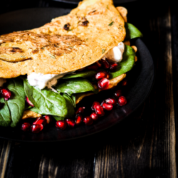 Tasty vegan omelette based on chickpea flour and tofu, with fresh spinach, vegan sour cream and pomegranate seeds